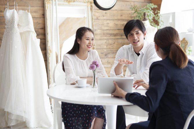 結婚式についてプランナーと話し合う新婚夫婦