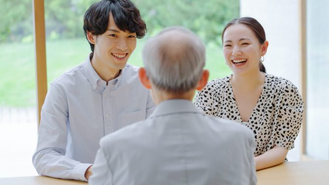 会話をするシニア男性と若い男女