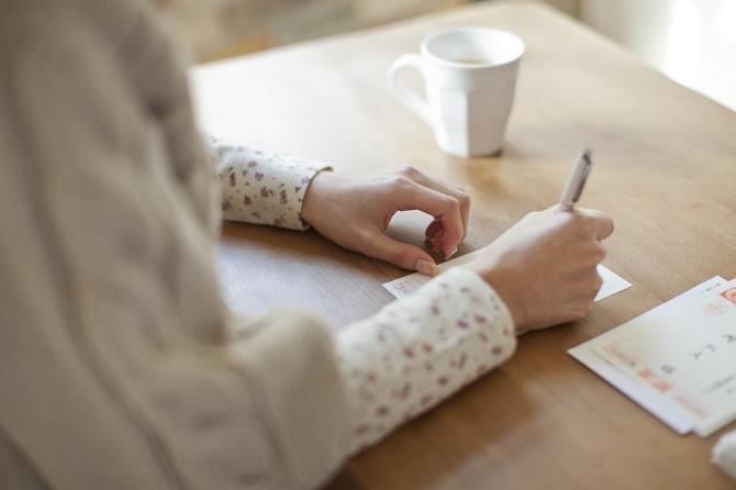 結婚報告のはがきを書く女性の手